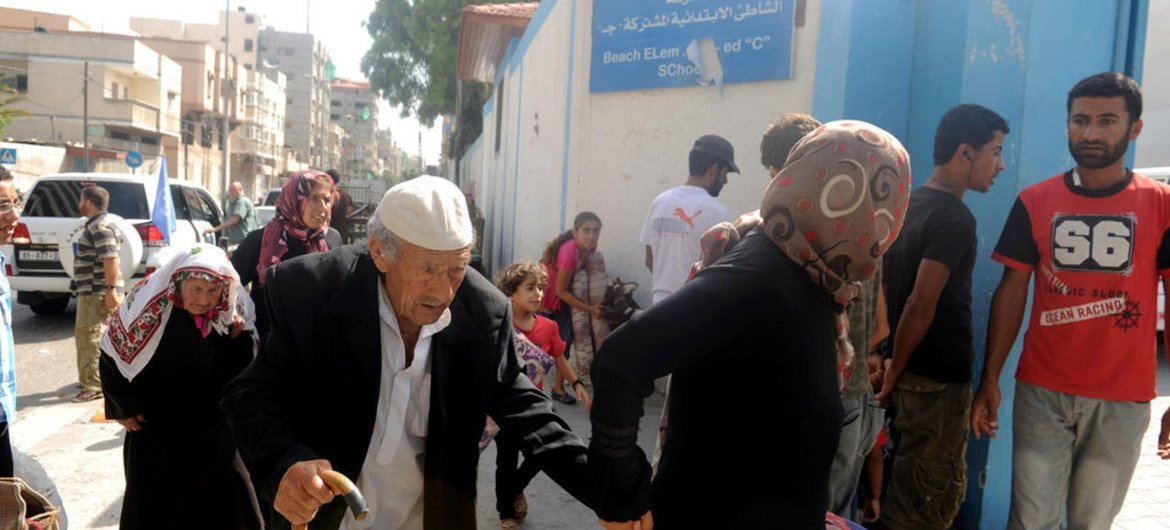 Palestinian families travel to a UNRWA school to seek shelter after evacuating their homes near the border in Gaza City.