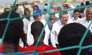 Secretary-General Ban Ki-moon (blue cap) chats with young Haitians at the opening of  the Sports for Hope Centre.
