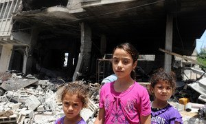 Palestinian children travel to an UNRWA school to seek shelter after evacuating their homes near the border in Gaza City on July 13, 2014.