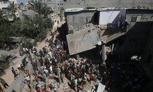 A large crowd gathers in front of a home that was destroyed during Israeli air strikes in the city of Khan Yunis in the southern Gaza Strip (8 July 2014). Repeated air strikes have destroyed many homes during the recent escalation of violence.
