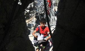 A boy looks through a schoolbook as he sits in the rubble of a home destroyed during an Israeli air strike on the city of Khan Yunis.