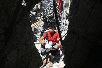 Un garçon regarde un manuel scolaire dans les décombres d'une maison détruite dans un bombardement israélien à Gaza en 2014. UNICEF/NYHQ2014-0894/El Baba