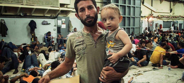 A bord d'un navire italien, un père syrien et son fils attendent de voir un médecin après avoir été sauvés en mer Méditerranée. Photo HCR/A. D'Amato