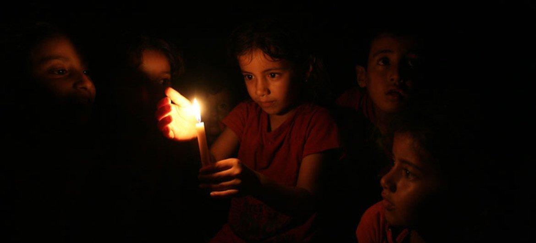 Niña palestina en Gaza utiliza una vela por carecer de electricidad. Foto de archivo: UNICEF/NYHQ2014-0982/El Baba