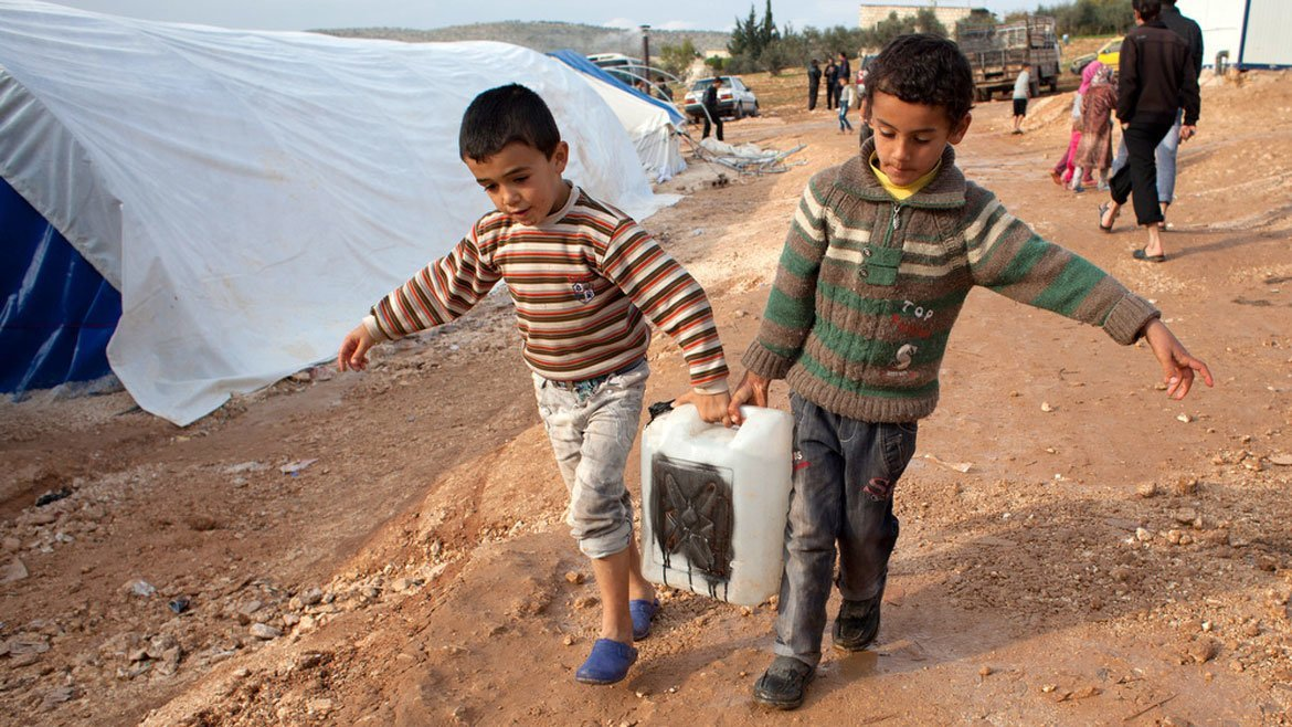 Two young boys carry water at Qah, a makeshift camp for displaced people in northern Syria, near the Turkish border. The people here receive limited and irregular amounts of humanitarian aid.