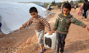Deux jeunes garçons portent de l'eau à Qah, un camp de fortune pour personnes déplacées dans le nord de la Syrie, près de la frontière turque. Photo IRIN/Jodi Hilton
