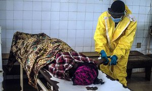 A government health worker at the Kenema Ebola Treatment Centre in Sierra Leone attends to a victim.