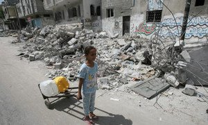 On 19 July 2014 in the State of Palestine, passing the rubble of homes destroyed in an Israeli air strike, a girl uses a hand truck to transport jerrycans filled with water, in the town of Rafah in southern Gaza.