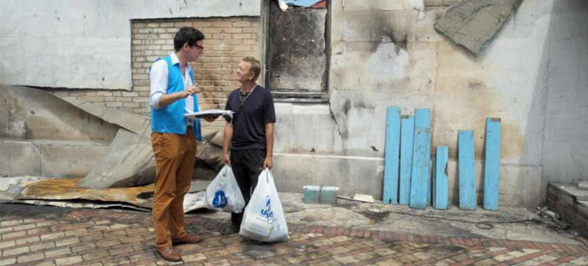 A UNHCR staff member asks a displaced Ukrainian man about the situation in his native Donetsk region, which has been heavily affected by the conflict.
