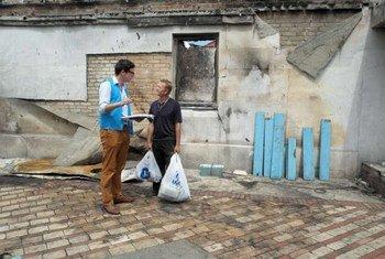 Un employé du HCR discute avec un déplacé ukrainien de la situation dans sa région natale de Donetsk (août 2014).  Photo HCR/I. Zimova