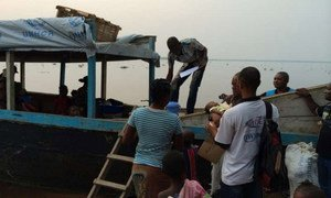 Refugees disembark from the boat that has brought them back home across the Oubangui River to the Democratic Republic of the Congo (DRC).