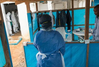 A woman waits to enter an  isolation ward to visit her husband, along with Liberian Ministry of Health, WHO, and Médecins Sans Frontières (MSF) personnel who are treating several Ebola patients located in the capital Monrovia.