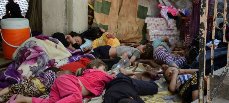 Members of an ethnic Yezidi family sleep in the shade in Shekhadi village, Iraq, after fleeing Sinjar.