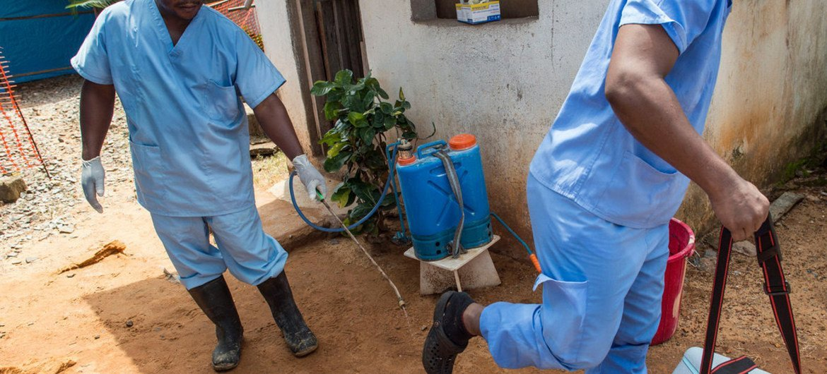 In the Liberian capital Monrovia, a Ministry of Health employee sprays the sole of a colleague's shoes at an Ebola Isolation Clinic, supported by the World Health Organization and Médecins Sans Frontières (MSF), as he prepares to leave the facility to carry blood samples to be tested.
