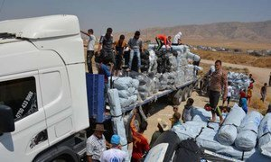 Workers unload trucks laden with hundreds of tents for families displaced by the recent fighting in Iraq.