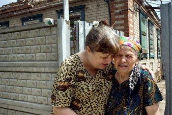 En Ukraine, en août 2014, une femme de retour à Sloviansk est réconfortée par une parente alors que sa maison a été frappée par un tir d'artillerie. Photo HCR/Iva Zimova