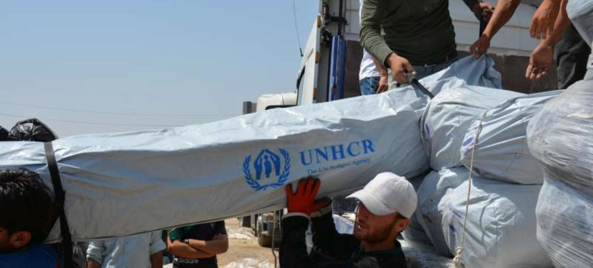 Workers unload trucks laden with hundreds of tents for families displaced by recent fighting in Iraq.