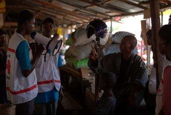 Des employés de l'UNICEF et d'organisations partenaires expliquent à des gens comment se protéger contre Ebola à Conakry, en Guinée. Photo UNICEF Guinée