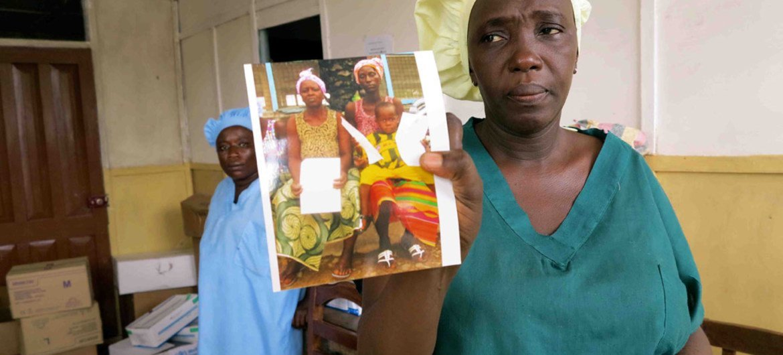 Une femme montre une photo de survivants qui ont quitté le centre de traitement d'Ebola à Kenema, en Sierra Leone. Photo UNICEF/Jo Dunlop