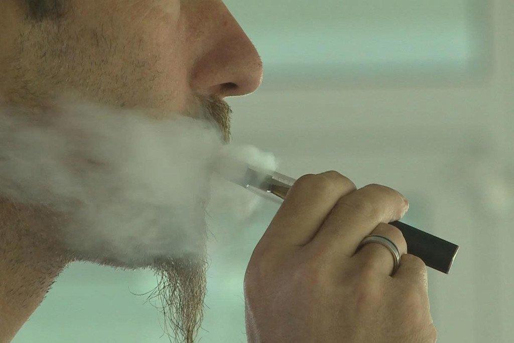 Un jeune homme fumant une cigarette électronique.