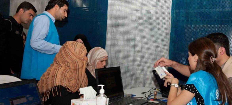 Ação de trabalhadores humanitários em Al Hassakeh verificando documentos de identidade de sírios em busca de assistência