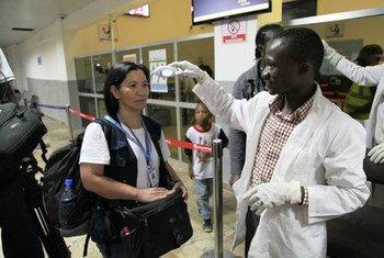Un employé de l'OMS vérifie la température d'une voyageuse à l'aéroport de Lugin, à Freetown, en Sierra Leone, en septembre 2014. Photo OMS Sierra Leone