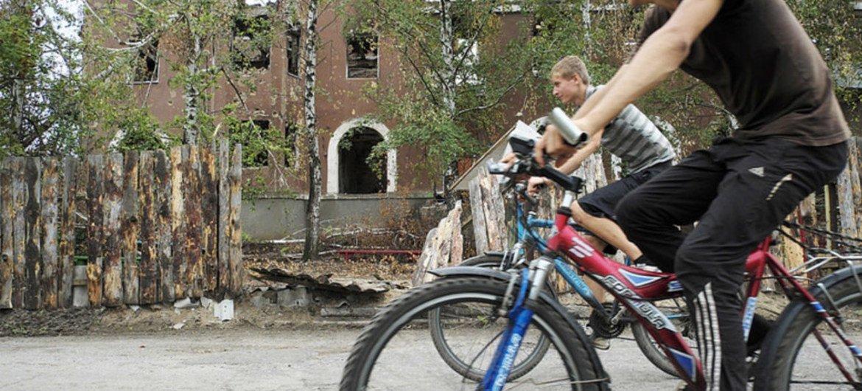 Лица, вернувшиеся в украинский Славянск,<br> проезжают  мимо поврежденных в ходе боев зданий.  <br> Фото УВКБ/ Ива Зимова