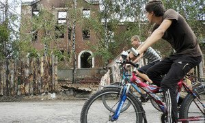 Returnees to the eastern Ukranian town of Sloviansk cycle past buildings that were heavily damaged during the fighting earlier in 2014.
