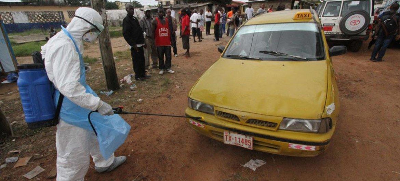 Un travailleur sanitaire désinfecte un taxi devant un centre de traitement de l'Ébola au Libéria.