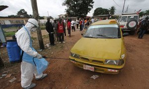 A health care worker disinfecting a taxi in Liberia at an Ebola treatment centre.