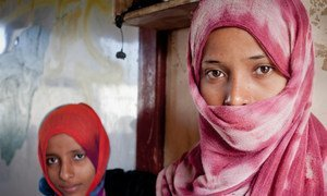 Two displaced girls stand in front of the classroom where their family has been living in Aden, Yemen (September 2012).
