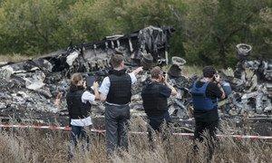Les membres de la Mission spéciale d'observation en Ukraine de l'Organisation pour la sécurité et la coopération en Europe (OSCE)  examinent le site du crash du vol MH17 de la Malaysia Airlines en juillet 2014.
