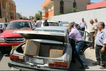 Une famille déplacée du gouvernorat de Ninive charge des paquets du PAM dans sa famille à un site de distribution à Erbil. Photo PAM/Mohammed Albahbahani