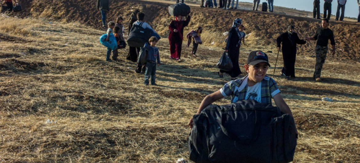 A Syrian boy, followed by his family runs with his bag moments after crossing the border into Jordan.