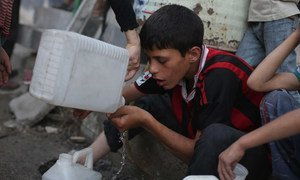A boy drinks the remaining water in his jerrycan while waiting with other children in a queue for safe water in the town of Douma in the East Ghouta area of Rural Damascus, Syria.