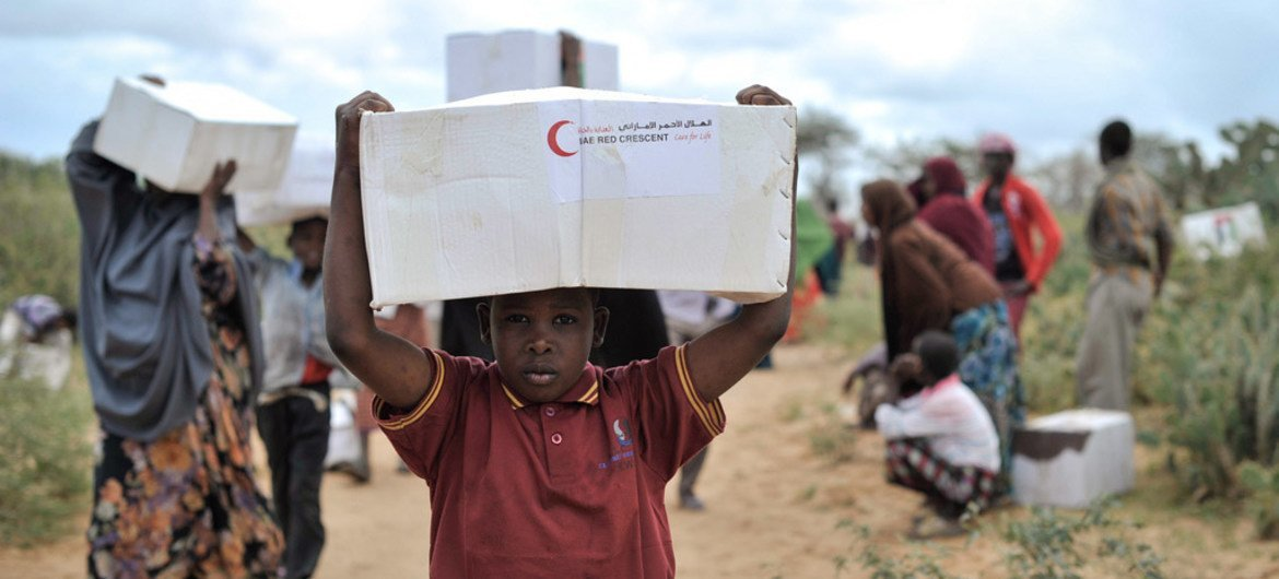 A young boy carries away a box of food from a distribution centre in Afgoye, Somalia.