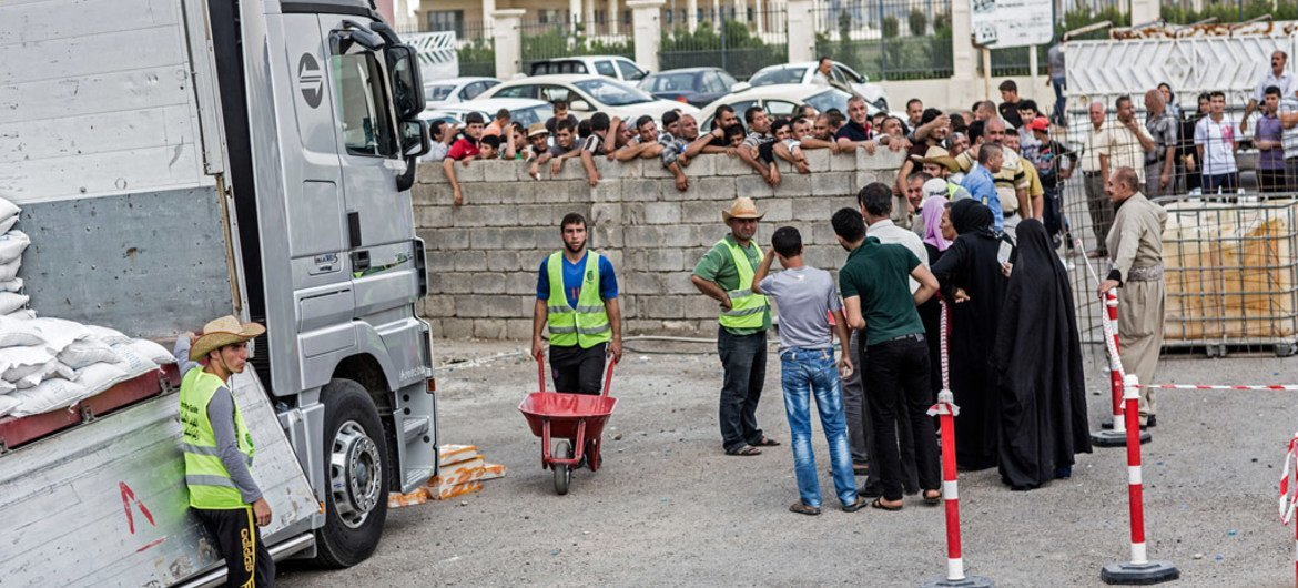 Displaced persons queue up to receive food supplies at a WFP distribution site in the Kasnazan area of Erbil Governorate, in northern Iraq.