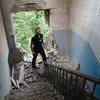 Un observateur de l'Organisation pour la sécurité et la coopération en Europe (OSCE) inspecte les dégâts causés à un bâtiment en Ukraine en juillet 2014.