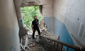 A monitor from the Organization for Security and Co-operation in Europe (OSCE) Special Monitoring Mission to Ukraine inspects damage to a building, 9 July 2014.