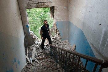 Un observateur de l'Organisation pour la sécurité et la coopération en Europe (OSCE) inspecte les dégâts causés à un bâtiment en Ukraine en juillet 2014. Photo OSCE/Evgeniy Maloletka