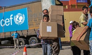 Displaced persons collect packages containing winter clothes and boots at a UNICEF distribution centre in Mangesh, a village in northern Iraq.