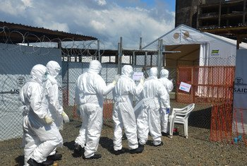 Health workers wearing personal protective equipment (PPE) walk in single file to a gate leading out of the green (safe) zone, at a newly built Ebola treatment unit (ETU) in Monrovia, Liberia.