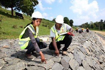 Working alongside her male team member, a female employee checks the quality of work at a dam under construction in Sri Lanka.