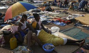 Members of one family uprooted when the violence erupted last year take shade and a rest under an umbrella at a site for internally displaced people in Bangui, Central African Republic (CAR).