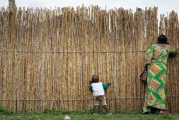 刚果民主共和国北基伍省,一位妇女和她的孩子隔着日托中心的竹篱笆向外张望。