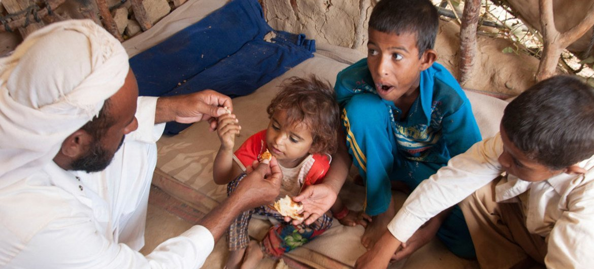 A family displaced by conflict in northern Yemen eats lunch in Al Mazraq, Hajjah.