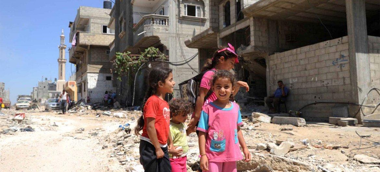加沙儿童在被毁的房屋前。近东救济工程处图片/Shareef Sarhan
