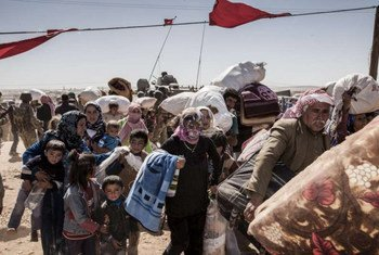 Syrian Kurdish refugees cross into Turkey from Syria near the town of Kobani.