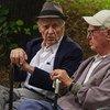 Deux hommes âgés discutent dans un parc.