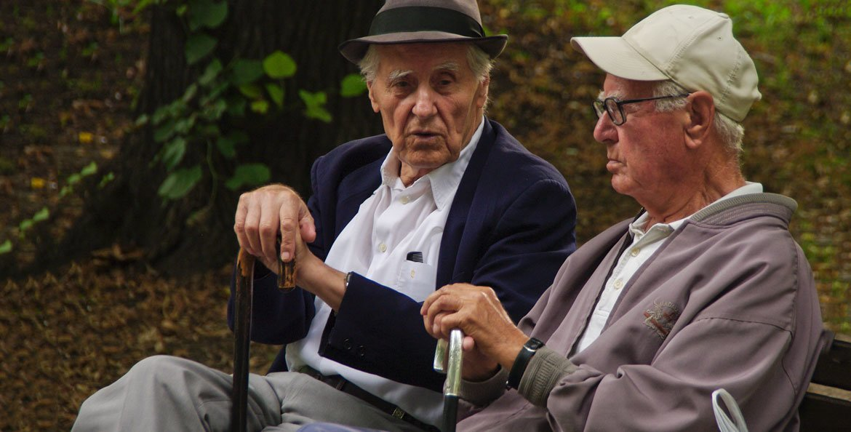 Dos hombres mayores conversan en el banco de un parque.